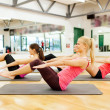 Stock Photo: Group of smiling women exercising on mats in gym