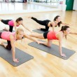 Stock Photo: Group of smiling women stretching on mats in gym