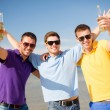 Male friends on the beach with bottles of drink — Stok fotoğraf
