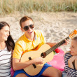 Group of friends with guitar having fun on beach — Stock Photo #42116177