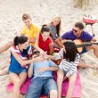 Group of friends with guitar having fun on beach — Stock Photo
