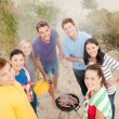 Stock Photo: Group of friends making barbecue on beach