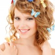 Happy teenage girl with butterflies in hair — Stock Photo #42116311