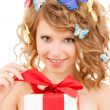 Teenager with butterflies in hair opening present — Stock Photo