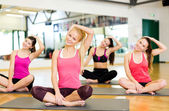 Group of smiling women stretching on mats in gym — Stok fotoğraf