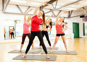 Group of smiling women stretching in the gym — Photo
