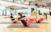 Group of smiling women exercising on mats in gym — Stok fotoğraf