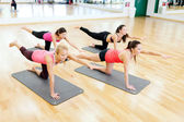 Group of smiling women stretching on mats in gym — ストック写真