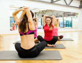 Group of smiling women stretching on mats in gym — Photo