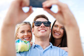 Friends taking picture with smartphone camera — Stock Photo