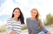 Smiling girlfriends having fun on the beach — Stock Photo