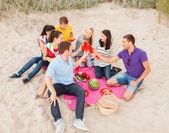 Group of friends celebrating birthday on beach — Stock Photo