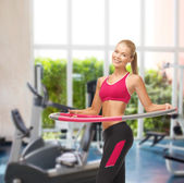 Young sporty woman with hula hoop at gym — Stock Photo