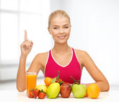 Mujer con jugos y frutas levantando el dedo — Foto de Stock