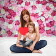 Happy mother with adorable little girl and heart — Stock Photo #42201007