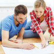 Smiling couple looking at blueprint at home — Stock Photo #42205917