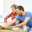 Stock Photo: Smiling couple unpacking kitchenwear
