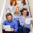 Stock Photo: Team with papers and take away coffee on staircase