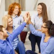 Stock Photo: Team doing high five gesture sitting on staircase