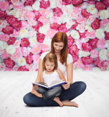 Happy mother with adorable little girl and book — Foto Stock