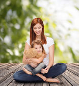 Happy mother with adorable girl and teddy bear — Foto Stock