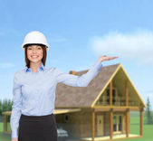 Businesswoman in helmet holding something on palm — Stock Photo