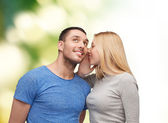 Smiling girlfriend telling boyfriend secret — Stock Photo
