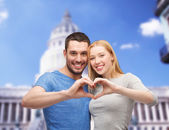 Smiling couple showing heart with hands — ストック写真