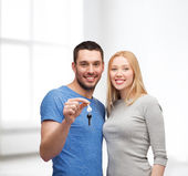 Smiling couple holding keys — Stock Photo