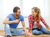 Smiling couple measuring wood flooring — Photo