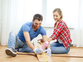 Smiling couple measuring wood flooring — Foto Stock