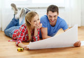 Smiling couple looking at blueprint at home — Stock Photo