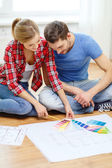 Smiling couple looking at color samples at home — Stock Photo