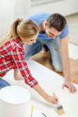 Smiling couple smearing wallpaper with glue — Stockfoto