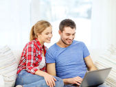 Smiling couple with laptop computer at home — Stok fotoğraf