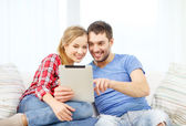 Smiling couple with tablet pc computer at home — Stok fotoğraf