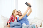 Smiling couple with tablet pc computer at home — Photo
