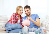 Smiling couple with piggybank sitting on sofa — Stock Photo