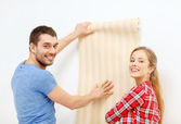 Smiling couple choosing wallpaper for new home — Stock Photo
