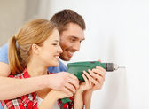 Smiling couple drilling hole in wall at home — Stock Photo
