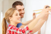 Smiling couple measuring wall — Foto Stock