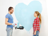 Smiling couple painting big heart on wall — Stock Photo