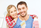 Smiling couple covered with paint with paint brush — Foto Stock