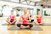 Group of smiling feamle meditating in the gym — Stock Photo