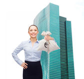 Young businesswoman holding money bags with euro — Stok fotoğraf