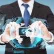 Businessman showing smartphone with globe hologram — Stock Photo