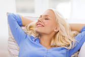 Smiling young woman lying on sofa at home — Stockfoto