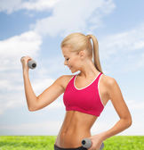 Young sporty woman with light dumbbells outdoors — Stok fotoğraf