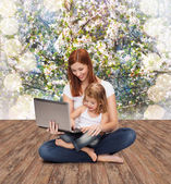 Happy mother with adorable little girl and laptop — ストック写真