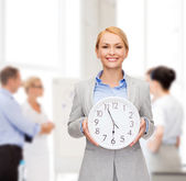Smiling businesswoman with wall clock — Stock Photo